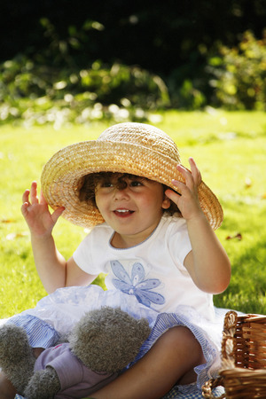 picnicking: Young girl playing with hat while picnicking in the park