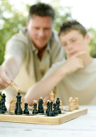 Father and son playing chess game photo