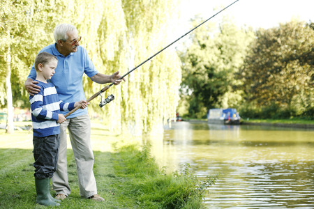 Senior man fishing with his grandson photo
