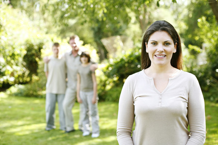 Woman smiling at the camera with her family standing in the background