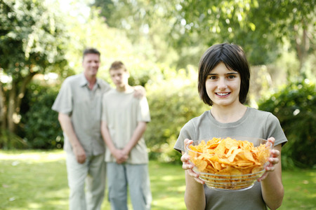 he   my sister: Teenage girl holding a bowl of chips with her brother and father standing in the background