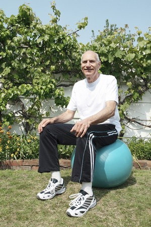 Senior man sitting on fitness ball photo