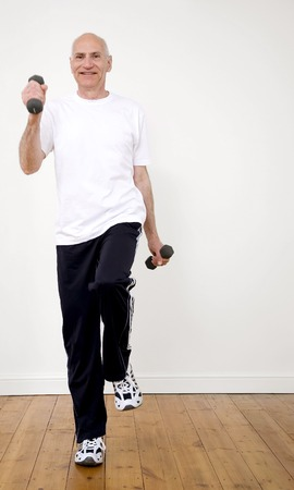 Senior man standing on one leg, lifting dumbbells photo