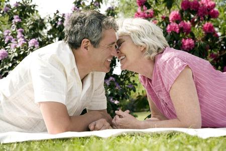 picnic blanket: Hombre mayor y mujer frota la nariz mientras est� acostado hacia adelante en la manta de picnic