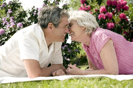 Senior man and woman rubbing nose while lying forward on picnic blanket photo