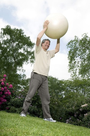 Senior man holding fitness ball photo