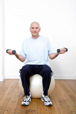Senior man sitting on gym ball while lifting up dumbbells photo