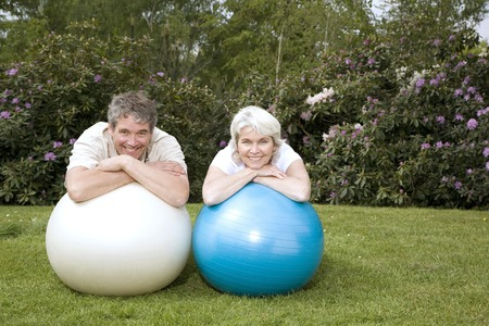 Senior man and woman resting on fitness ball photo