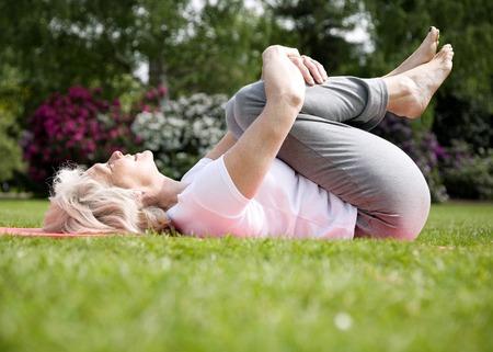 hugging knees: Senior woman lying on her back hugging her knees