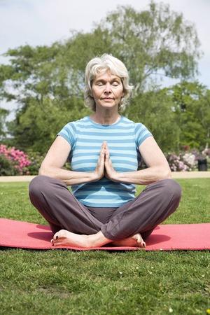 Senior woman with legs crossed, practising yoga photo