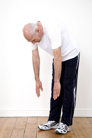 bending down: Senior hombre agachado, tratando de llegar a sus pies
