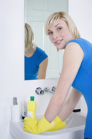 bathroom mirror: Woman with rubber gloves cleaning the sink Stock Photo