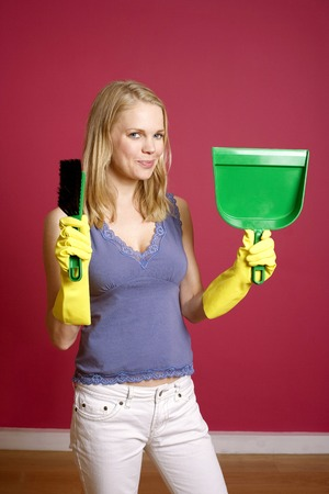 Woman with rubber gloves holding a hand broom and dust pan