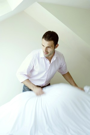 tidiness: Man making his bed Stock Photo