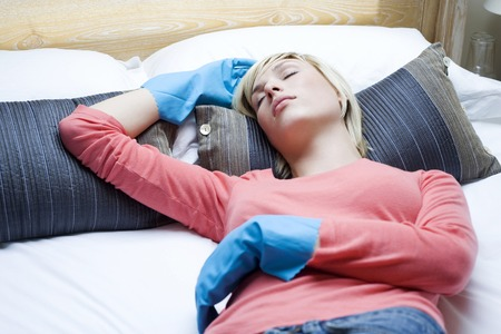 Woman with rubber gloves lying on the bed Stock Photo