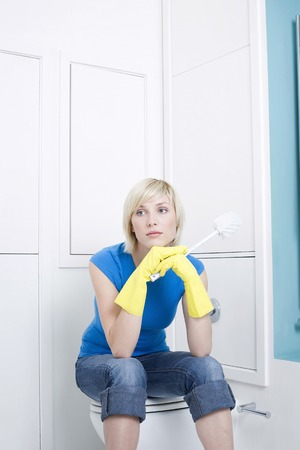 Woman with rubber gloves sitting on toilet bowl, holding a cleaning brush photo