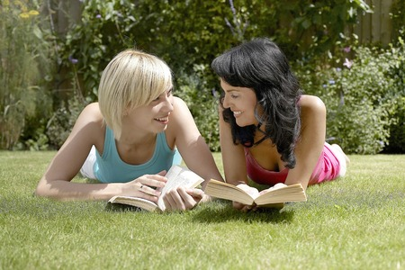 lying forward: Two women reading at the park Stock Photo
