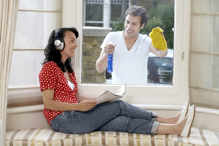 Man cleaning the window while woman is listening to music on headphones and reading a magazine photo