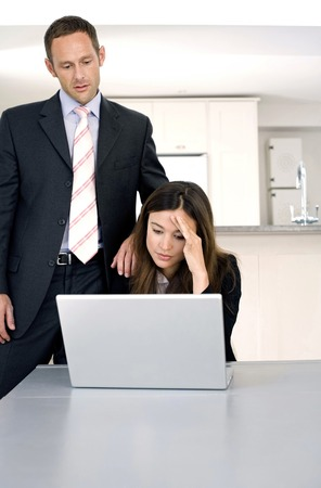 Businesswoman working on laptop with businessman looking on photo