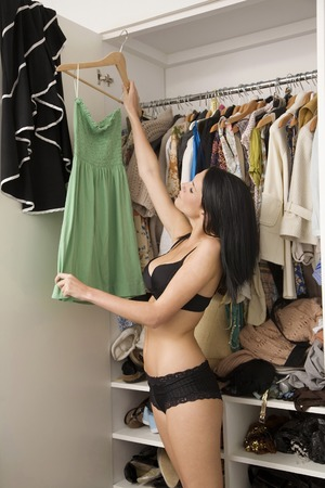 choosing clothes: Woman choosing clothes from the wardrobe
