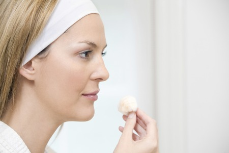 toning: Woman cleaning her face with cotton wool