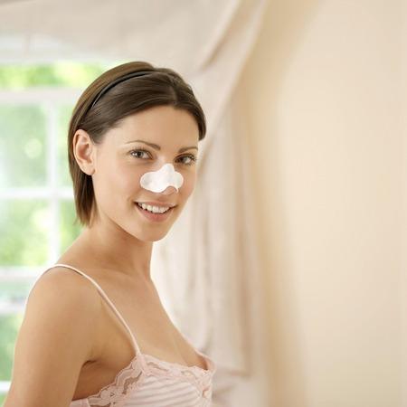 pore: Woman using pore strip