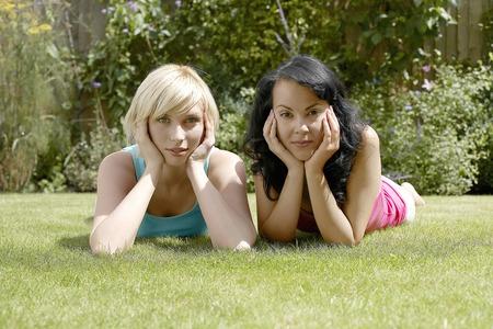 lying forward: Two women lying forward on the grass