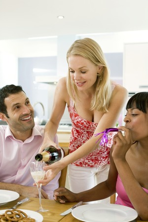 Woman pouring champagne for her guests photo