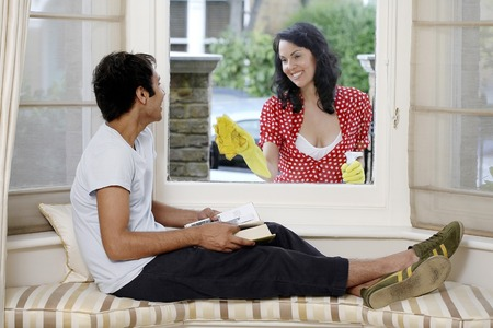 Woman cleaning window while a man is reading a book inside photo