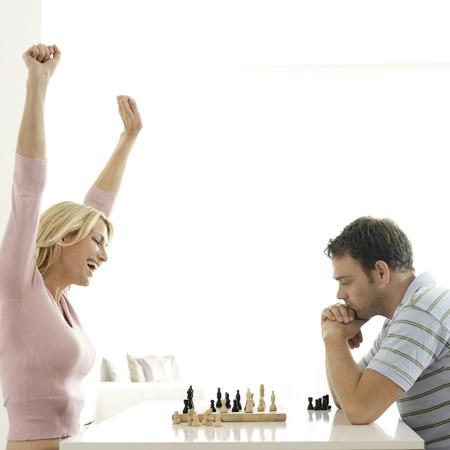 jubilating: Man and woman playing chess game