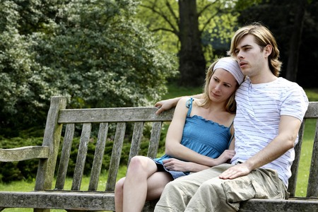 he she: Man and woman sitting on a bench at the park Stock Photo