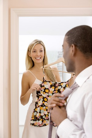 Man adjusting his necktie, woman holding blouse on clothes hanger in the background photo