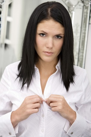 buttoning: Woman buttoning her shirt