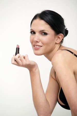 Woman smiling at the camera while holding lipstick photo