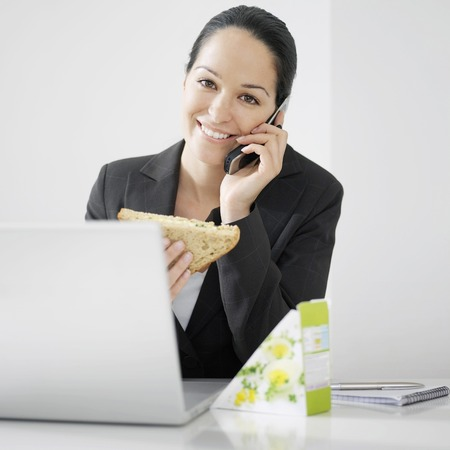 Businesswoman holding sandwich while talking on the phone photo