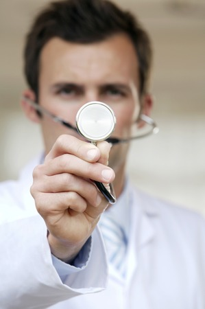 seriousness skill: Male doctor holding up a stethoscope towards the camera