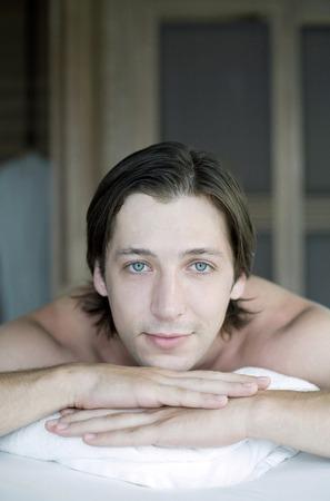 lying forward: Man lying  forward on massage table, looking at the camera Stock Photo