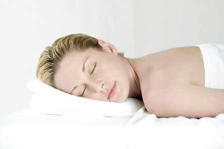Woman lying forward on massage table with her eyes closed Stock Photo - 26224003