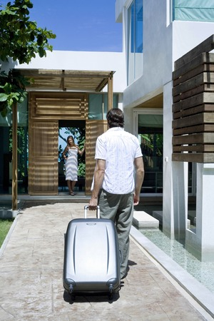 Man with his briefcase walking towards woman standing at the doorway photo