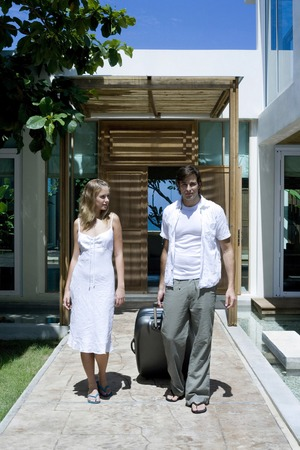 Man with briefcase and woman walking together at the resort photo