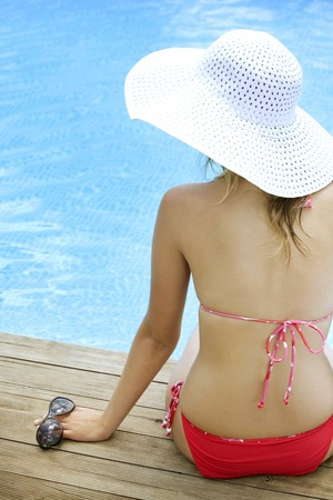 Woman in bikini wearing a straw hat, holding sunglasses photo