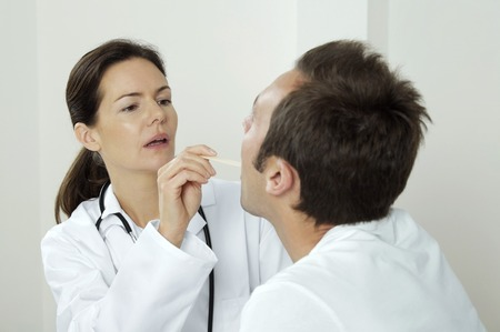 depressor: Female doctor using tongue depressor to examine her patient Stock Photo