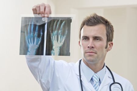 seriousness skill: Male doctor looking at x-ray