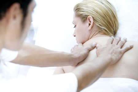 Massage therapist massaging woman's back photo