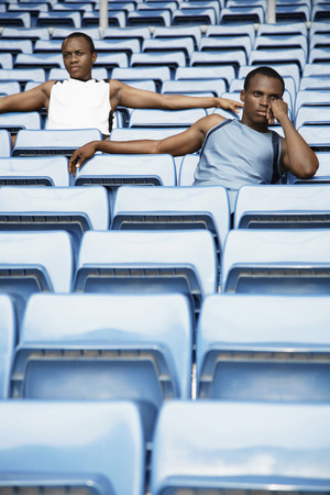 contemplates: Men sitting amongst rows of blue seats in stadium Stock Photo