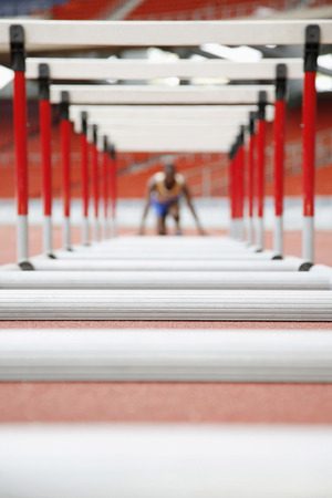 Man getting ready to jump hurdles Banco de Imagens