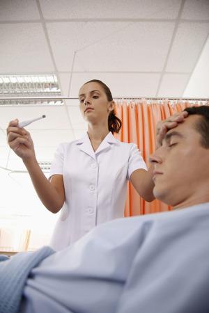 lies down: Nurse checking mans temperature