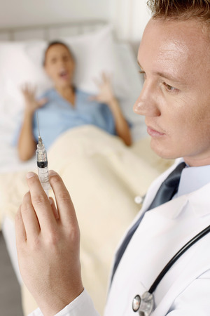Doctor holding syringe, patient screaming photo