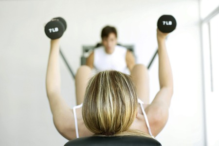 Woman lifting dumbbells with a man exercising in the background Stock Photo