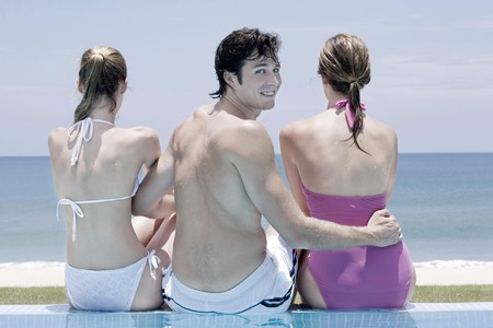 Man and women sitting by the poolside photo